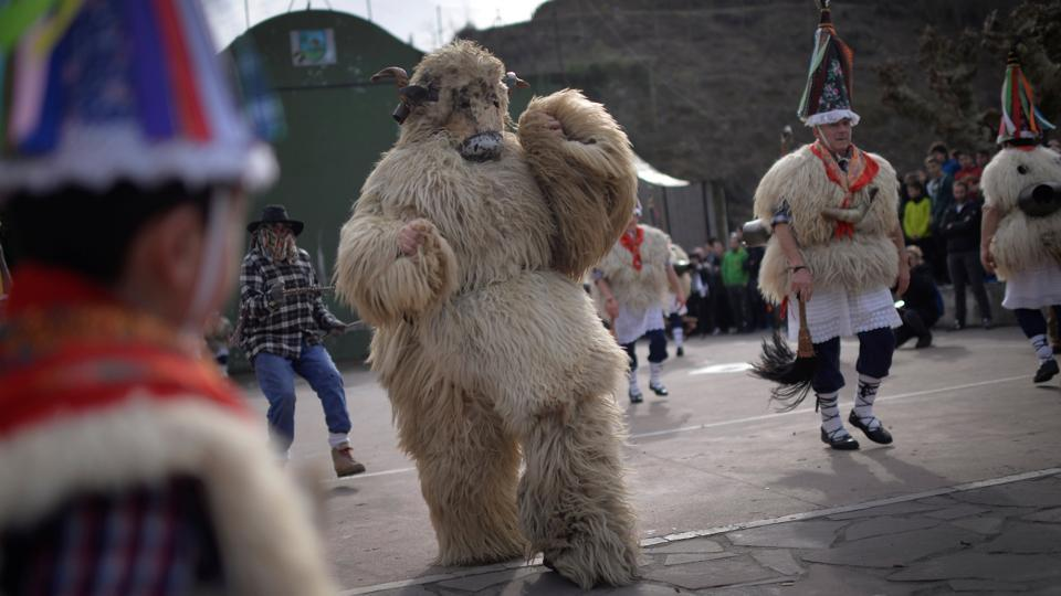 A masked reveller dressed as a bear performs alongside dancers.  (Reuters photo)