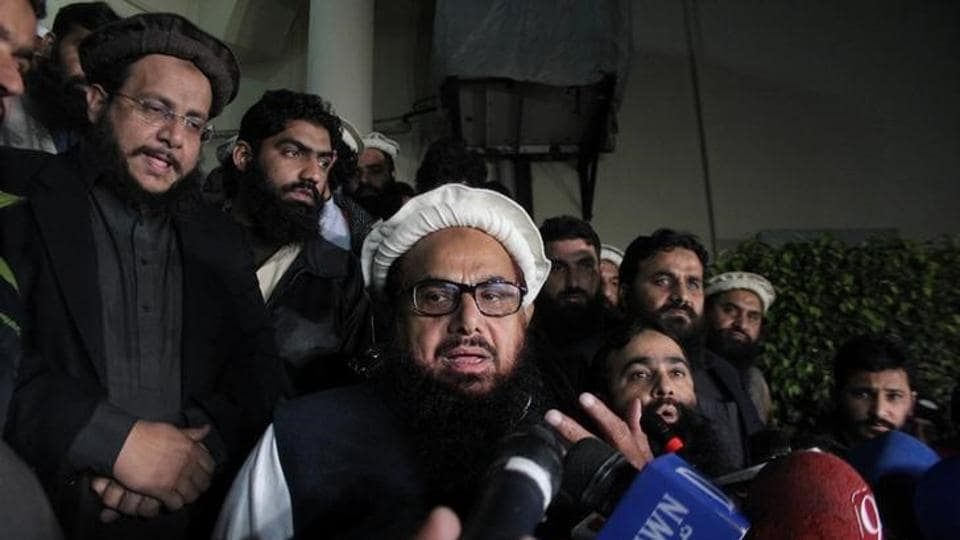 Hafiz Muhammad Saeed, chief of the banned Islamic charity Jamat-ud-Dawa, speaks with media as he is escorted to his home before being put under house arrest in Lahore, Pakistan.
