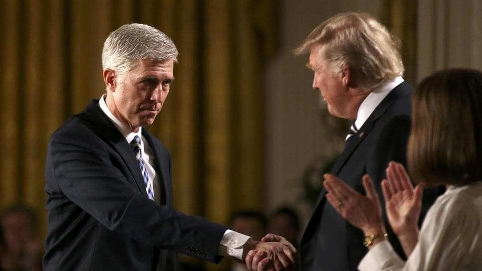 Judge Neil Gorsuch (L) shakes hands with US President Donald Trump as Gorsuch's wife Louise (R) applauds after President Trump nominated Gorsuch to be an associate justice of the US Supreme Court at the White House in Washington, DC.