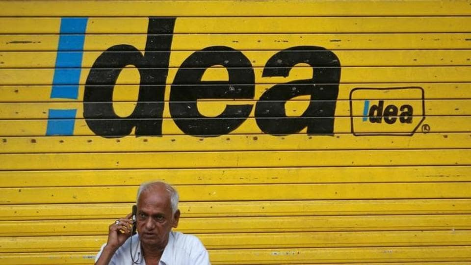 A man speaks on his mobile phone as he sits in front of a shop displaying the Idea Cellular Ltd's logo on its shutter in Mumbai.