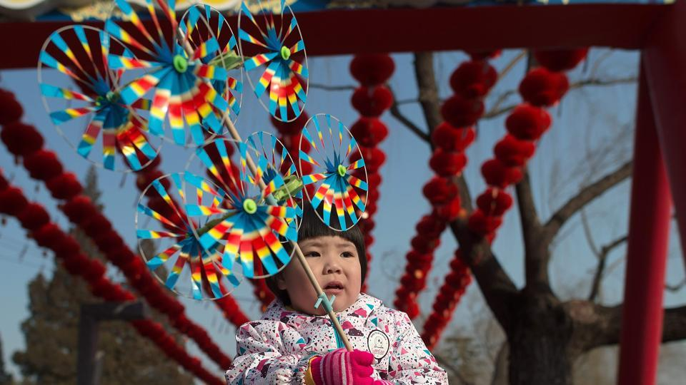A little girl holds colourful pinwheels at a Spring Festival fair. The holidays are a time for families to get together and go out to fairs and restaurants.  (Nicolas ASFOURI / AFP)