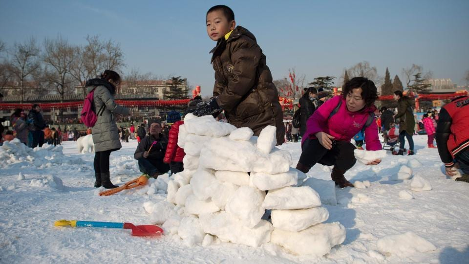 A boy constructs an igloo with snow at an amusement park during the Spring Festival holidays in Beijing. For the Chinese, the Spring Festival is like Christmas in the West, with a spirit of festivity pervading the air.  (Nicolas ASFOURI / AFP)