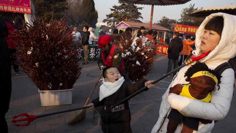 A child swings a toy weapon at a woman during a Spring Festival carnival in Beijing. A series of activities such as lion dancing, dragon lantern dancing, lantern festivals and temple fairs are held for the week.   (Ng Han Guan / AP)