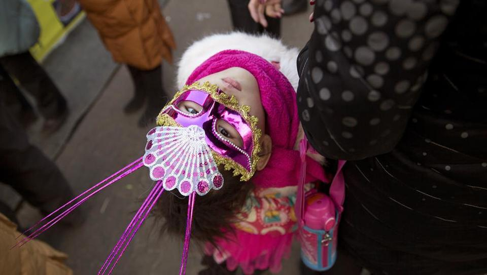 A child wears a carnival mask during a visit to a Spring Festival carnival in Beijing, China, on  January 31, 2017. Residents are enjoying a week long holiday for the Chinese New Year and visiting various temple fairs and carnivals around the Chinese capital. (Ng Han Guan / AP)