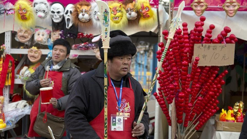 A vendor waits for customers to buy toy weapons at a Spring Festival carnival in Beijing. Shops and kiosks at the fairs do brisk business as people buy new clothes and gifts.  (Ng Han Guan / AP)