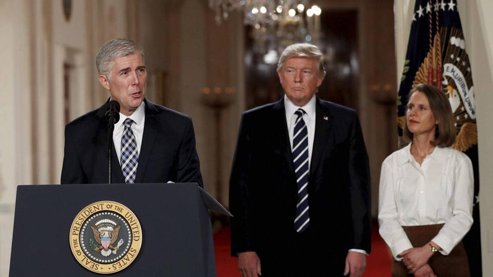 Judge Neil Gorsuch speaks as his wife Louise and President Donald Trump stand with him on stage in East Room of the White House in Washington on Tuesday.