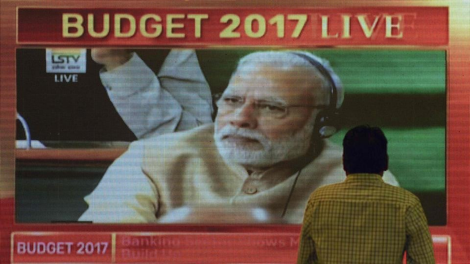 An office-worker walks past a digital screen showing Indian Prime Minister Narendra Modi during Finance Minister Arun Jaitley delivering the budget speech at Parliament at the Bombay Stock Exchange (BSE) in Mumbai on February 1, 2017.