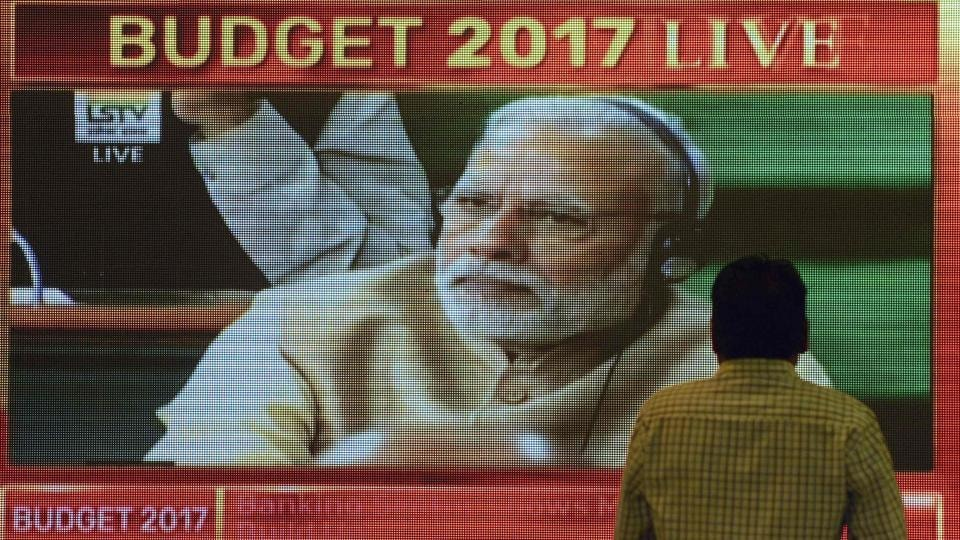 An Indian office-worker walks past a digital screen showing Indian Prime Minister Narendra Modi during finance minister Arun Jaitley delivering the budget speech at Parliament at the Bombay Stock Exchange (BSE) in Mumbai.