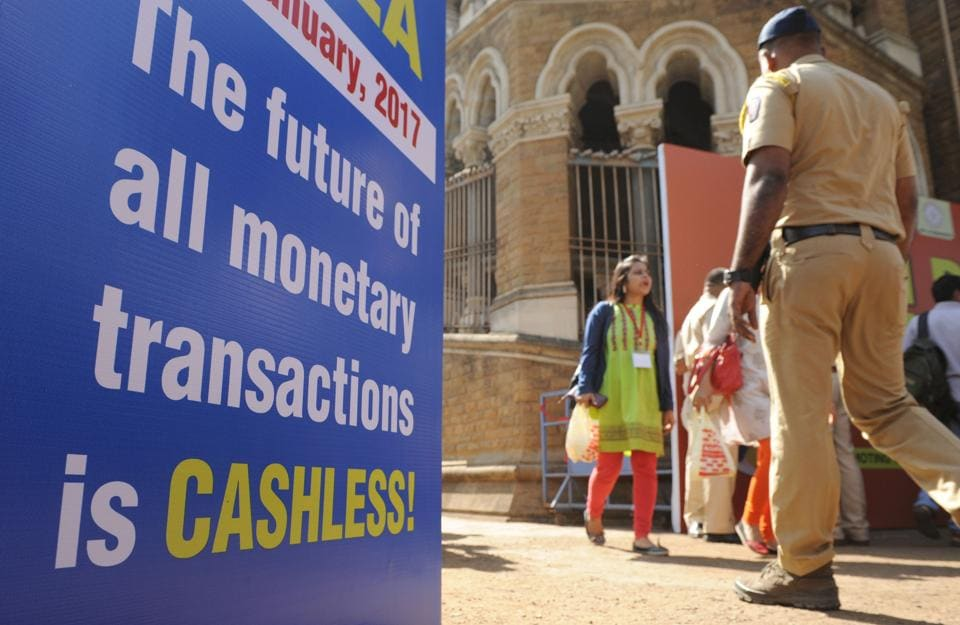 Visitors walk past a sign for a digital or cashless economy at a Digital Wealth Fair promoting e-payments in Mumbai.