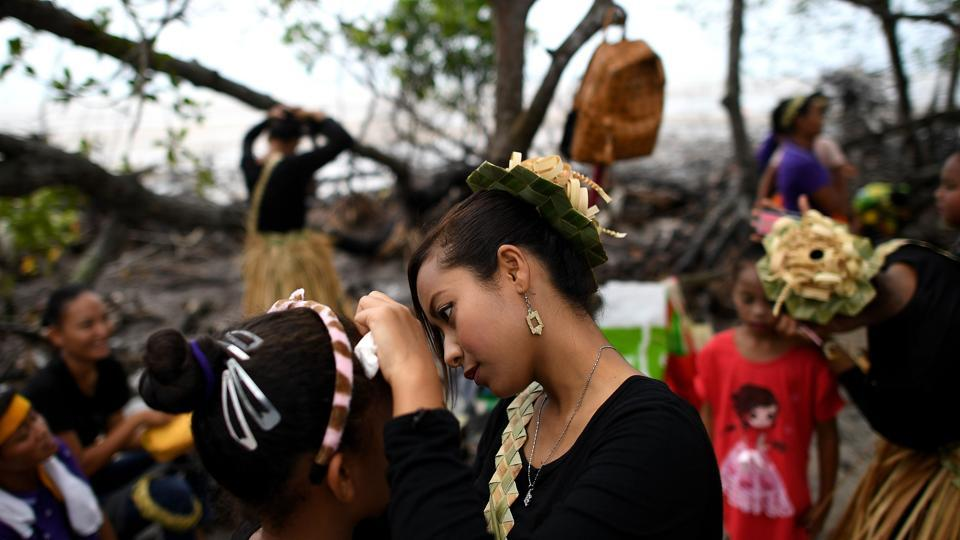 A Malaysian indigenous Mah Meri tribeswoman (centre) applies makeup on a girl as they prepare for the Puja Pantai ritual, a thanksgiving ritual praying to the spirits of the seas, in Pulau Carey on the outskirts of Kuala Lumpur on February 1, 2017.  (Manan VATSYAYANA / AFP)