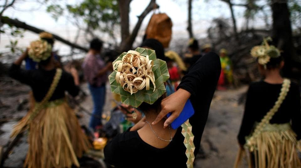 A Malaysian indigenous Mah Meri tribalwoman (C) ties her necklace before the start of the