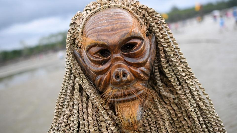 A Malaysian indigenous Mah Meri tribesman wears a traditionally crafted mask during the Puja Pantai ritual, a thanksgiving ritual praying to the spirits of the seas, in Pulau Carey on the outskirts of Kuala Lumpur on February 1, 2017.  (Manan VATSYAYANA / AFP)