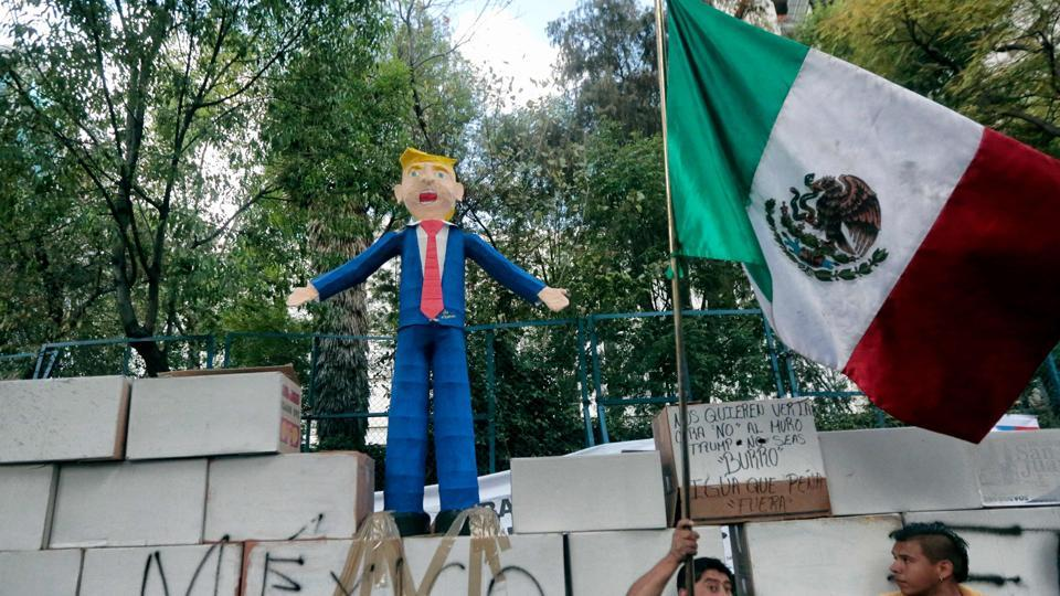 People protest against US President Donald Trump's inauguration next to a fake wall with a Mexican national flag and a dummy representing him in Mexico City.