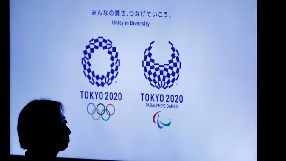 A woman is silhouetted against a monitor showing Tokyo 2020 Olympics and Paralympics emblems during the Olympic and Paralympic flag-raising ceremony at Tokyo Metropolitan Government Building on September 21, 2016.