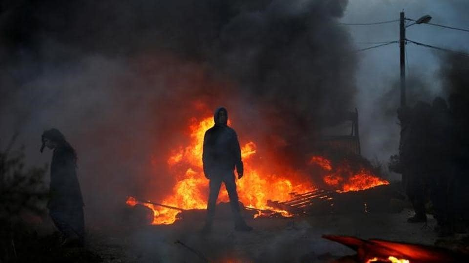 Protesters stand next to fire at the entrance to the Israeli settler outpost of Amona in the occupied West Bank.