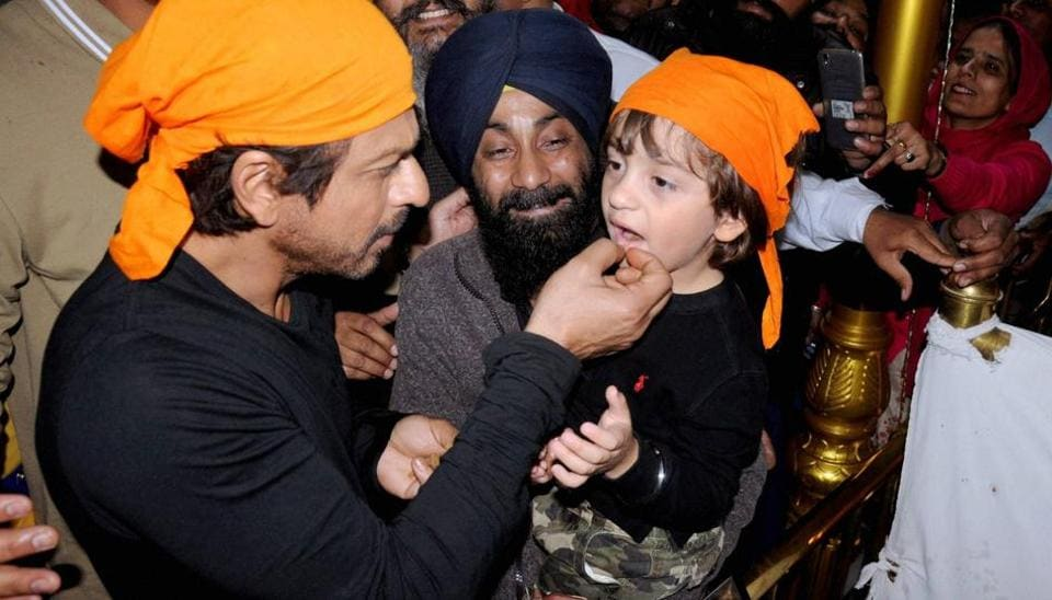 Shah Rukh Khan giving 'parshad' to his son AbRam while paying obeisance at Golden temple in Amritsar. (PTI)