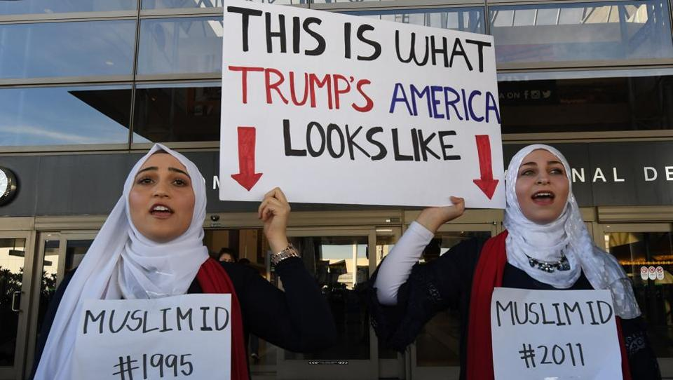 Noor Hindi (L) and Sham Najjar (R) who were born in the US of Syrian parents, demonstrate against the immigration ban imposed by US President Trump at the Los Angeles International Airport, California.  India's citizenship amendment bill openly discriminates against Muslim immigrants from the three specified countries.