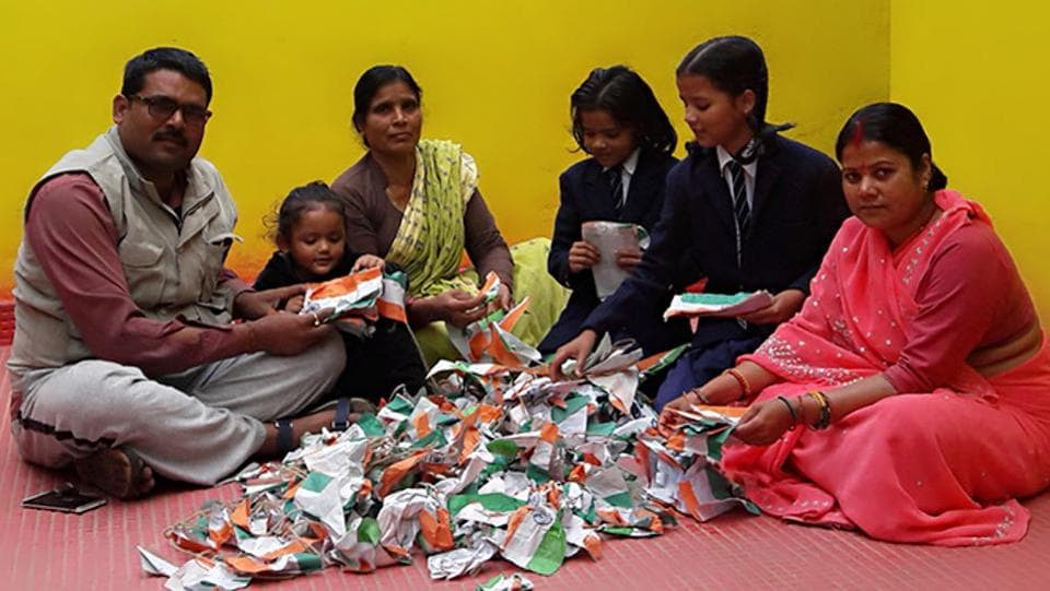 Businessman Anil Choudhary sits with his family sifting the tricolour.