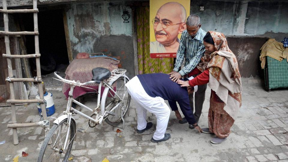 Sham Lal Gandhi, a follower of Mahatma Gandhi's philosophy, seeking blessings from his parents before filing his nomination papers for the upcoming Assembly elections as an independent candidate in Amritsar. (PTI)