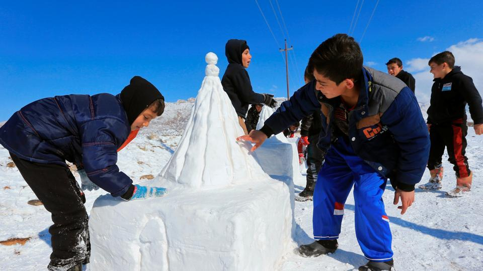 Displaced children who fled from Islamic State militants play with snow at a camp in Duhok, Iraq.