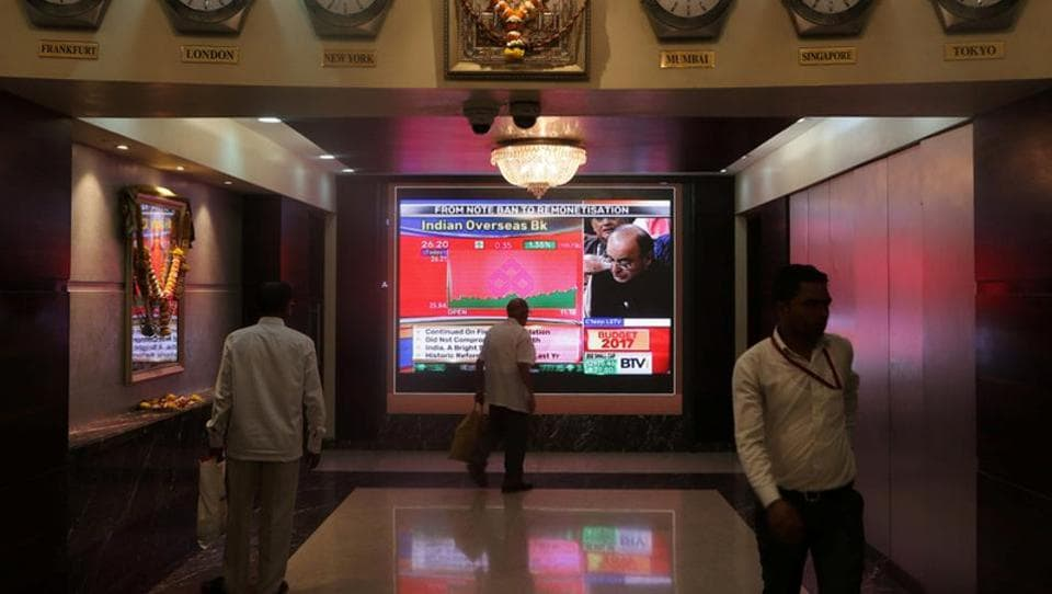 People walk as a telecast of finance minister Arun Jaitley presenting the budget is displayed inside the Bombay Stock Exchange (BSE) building in Mumbai.
