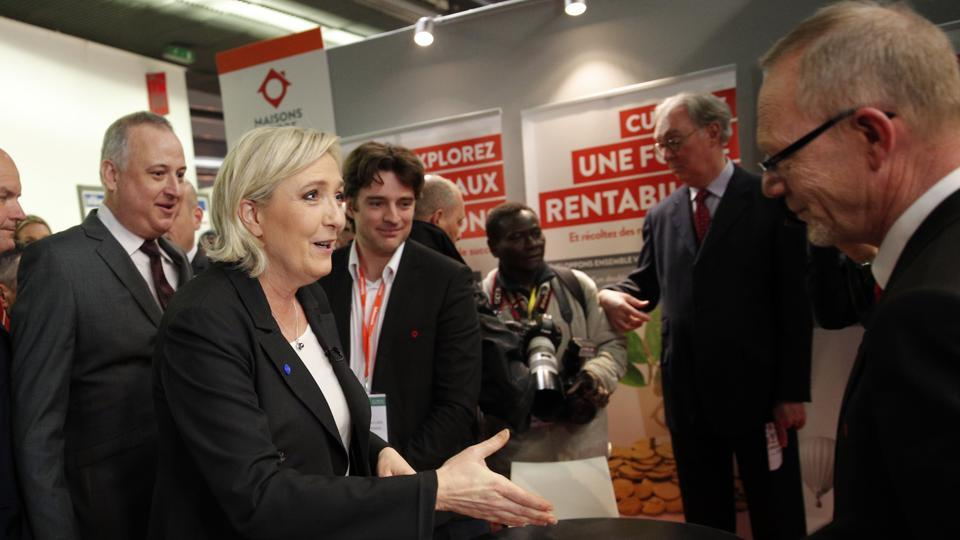 Far-right leader and candidate for next spring presidential elections Marine le Pen, centre left, shakes hands as she visits the Entrepreneur Fair in Paris, France.