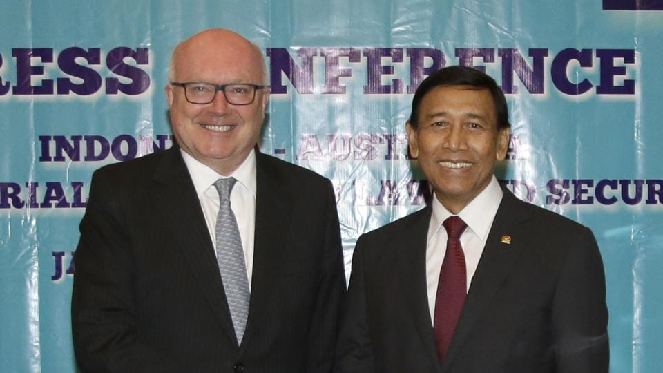 Australia's attorney general George Brandis, left, and Indonesian coordinating minister for security Wiranto pose for photographers as they shakes hands at the end of a press conference after their meeting at the ministerial council meeting on law and security in Jakarta, Indonesia,  Feb 2.