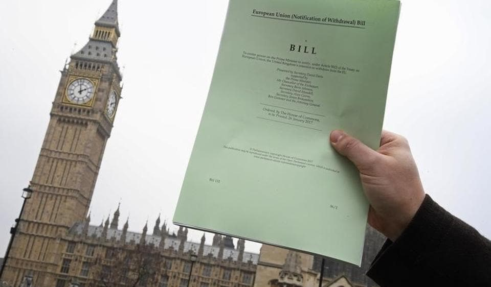 A journalist holds a copy of the Brexit Article 50 bill in front of the Houses of Parliament in London.