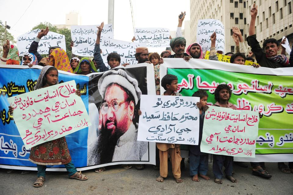 Pakistani demonstrators hold placards and banners during a protest after Jamaat-ud-Dawa (JuD) leader Hafiz Saeed was placed under house arrest in Karachi.