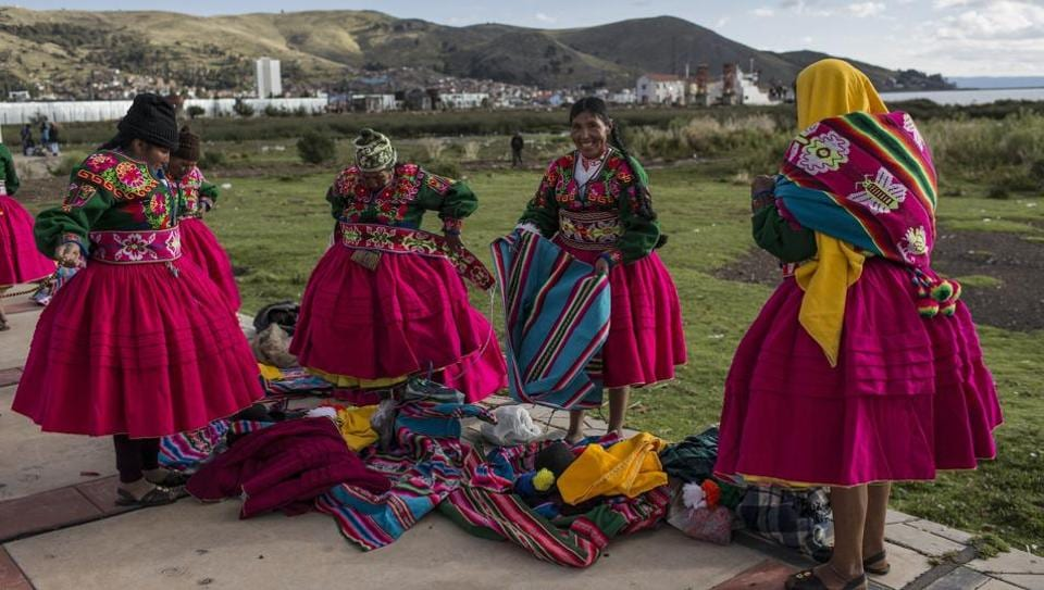 Dancers put on their costumes near the shore of Lake Titicaca prior to their performance for Virgin of Candelaria celebrations in Puno, Peru. Some competing groups wear shoes made of alpaca skin, collars hung with ears of corn and hats adorned with old coins or the bright-colored feathers of Amazonian birds.   (Rodrigo Abd / AP)