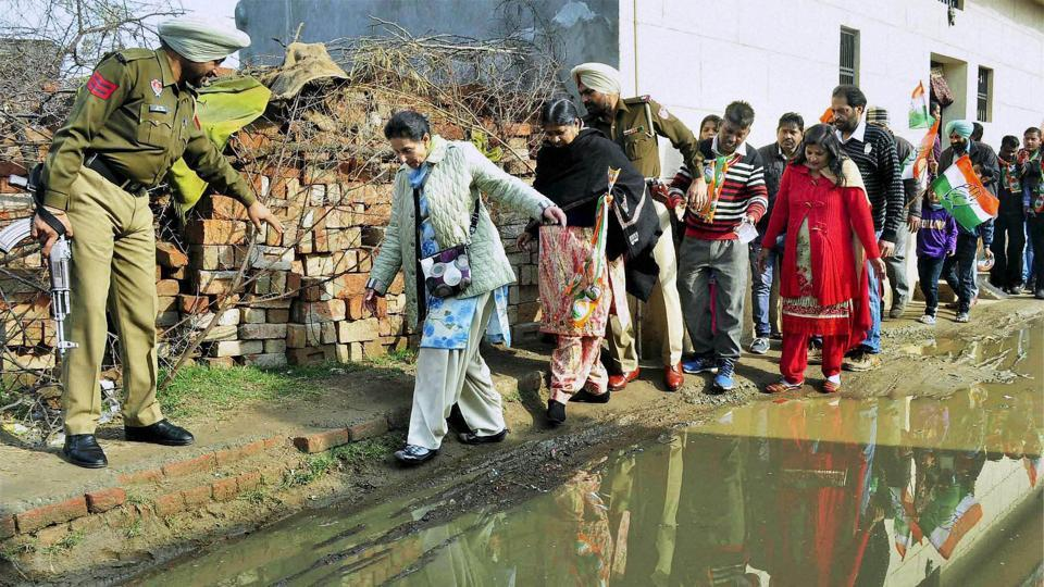 Patiala MLA Preneet Kaur walks cautiously at a waterlooged road during an election campaign for her husband Capt Amrinder Singh in Patiala. (PTI)