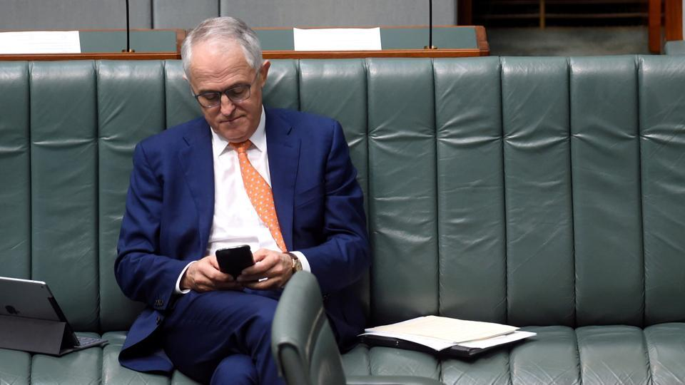 Australian Prime Minister Malcolm Turnbull uses his phone in the House of Representatives at Parliament House in Canberra.