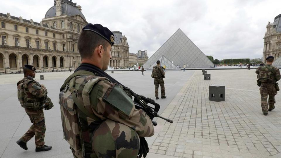 French army soldiers patrol near the Louvre Museum Pyramid's main entrance in Paris, France