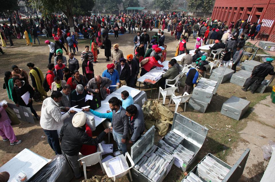 Polling officials collect electronic voting machines (EVM) at a distribution centre in Dera Bassi in Punjab on Friday on the eve of the state assembly elections.