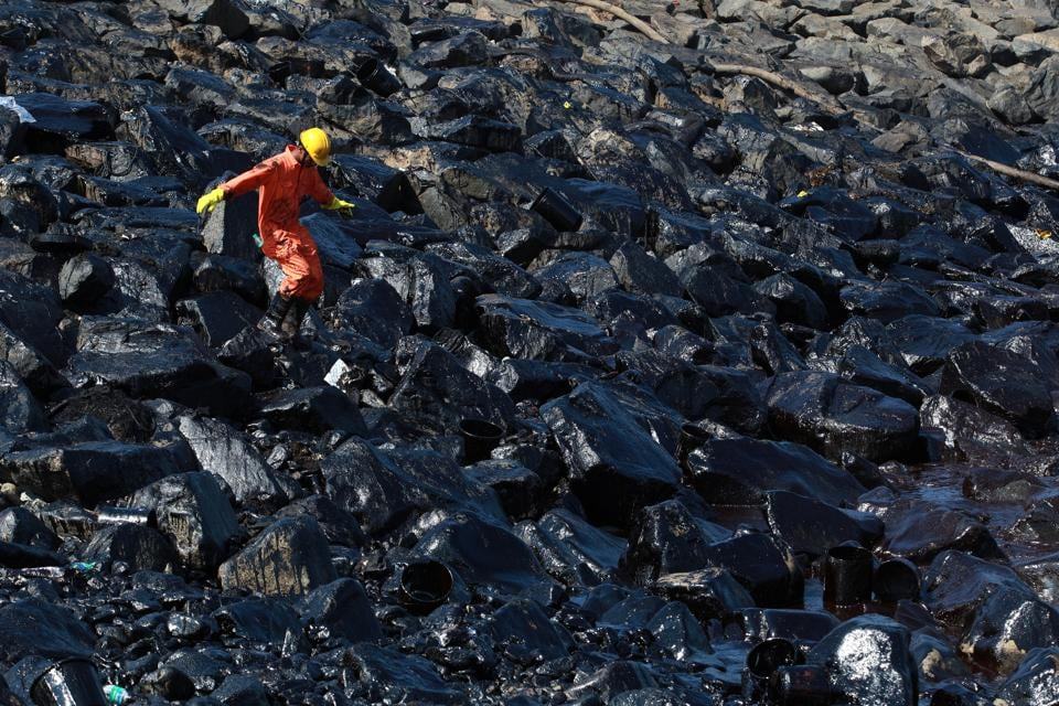 An emergency worker walks amidst oil deposits as he cleans oil from the shoreline of Ennore port in Chennai.