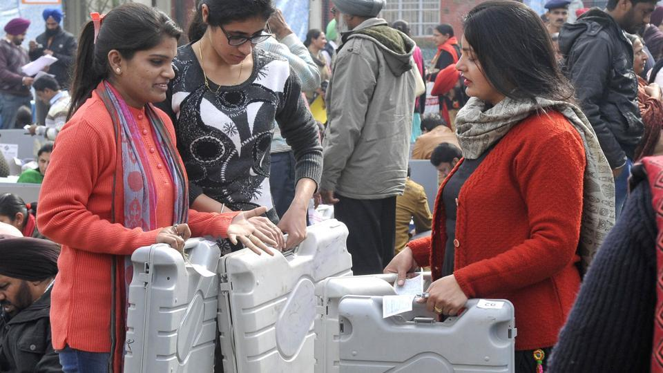 Poll staff members with EVMs at Khalsa College for Women, in Ludhiana on Friday. (Gurminder Singh/HT)