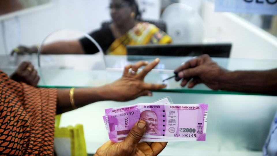 In this photograph taken on November 17, a woman holds Rs 2000 notes as she has her finger marked with indelible ink after exchanging 500- and 1000- rupee banknotes at a bank in Chennai.