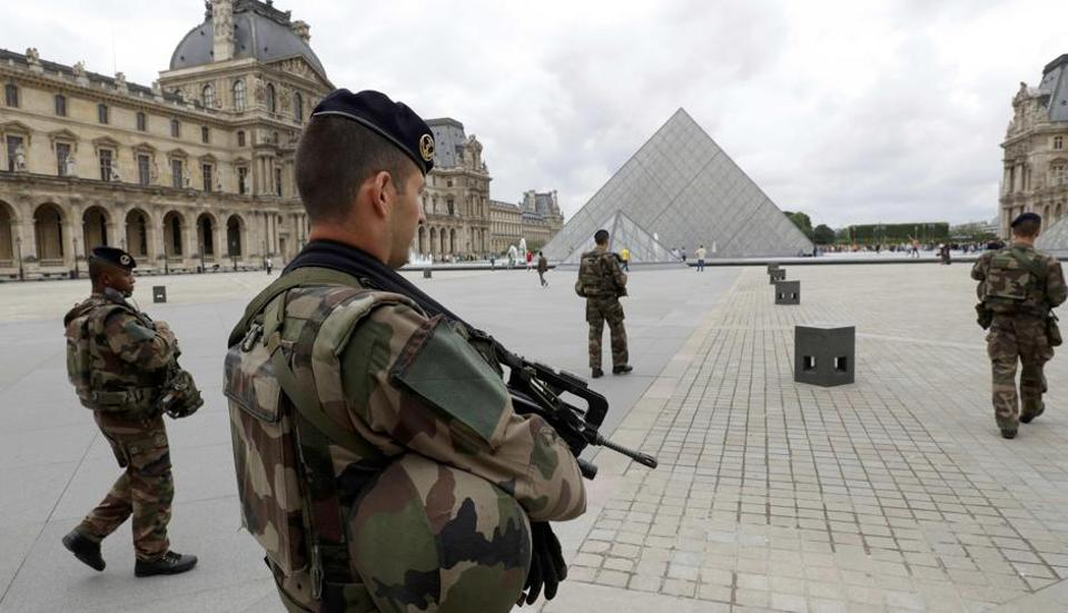 French army soldiers patrol near the Louvre Museum Pyramid's main entrance in Paris, France.