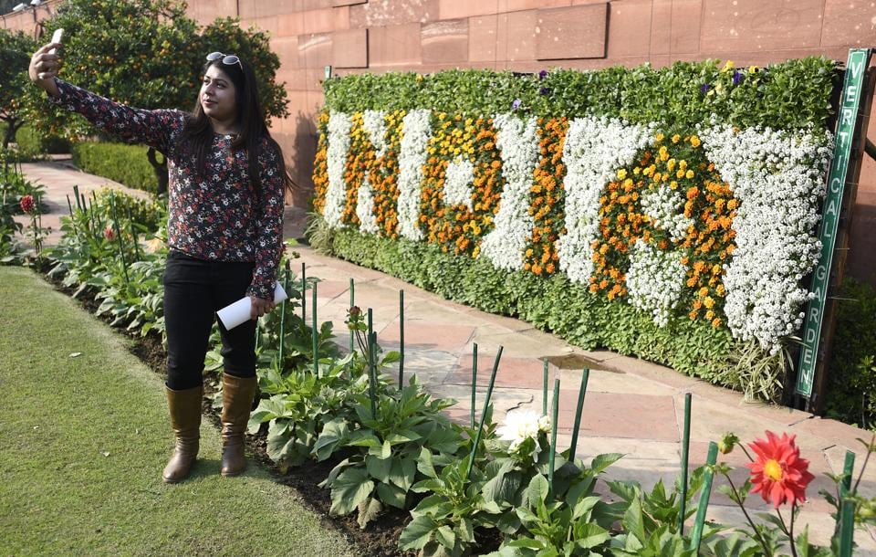 A visitor click selfie with flower decorated plaque at Mugha Gardens. The garden will be open for visitors till March. (Sonu Mehta/HT PHOTO)