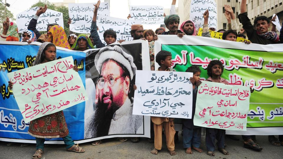 Demonstrators hold placards and banners during a protest after Jamaat-ud-Dawa (JuD) organisation leader Hafiz Saeed was placed under house arrest in Karachi.