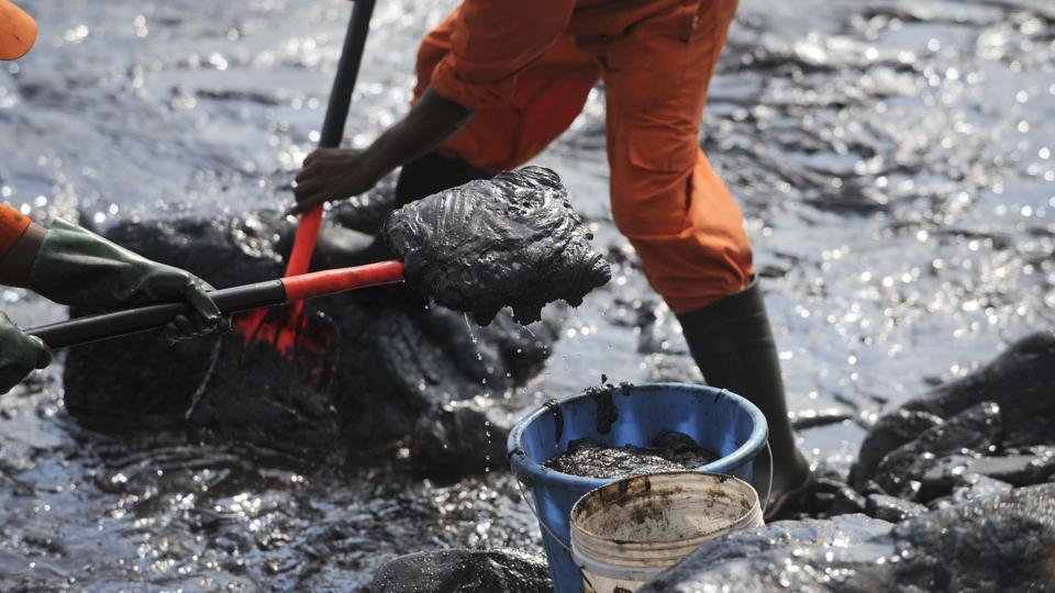 Members of Pollution Response Team of the Indian Coast Guard tackle the oil spill from boulders at the Ennore coast, in Chennai.