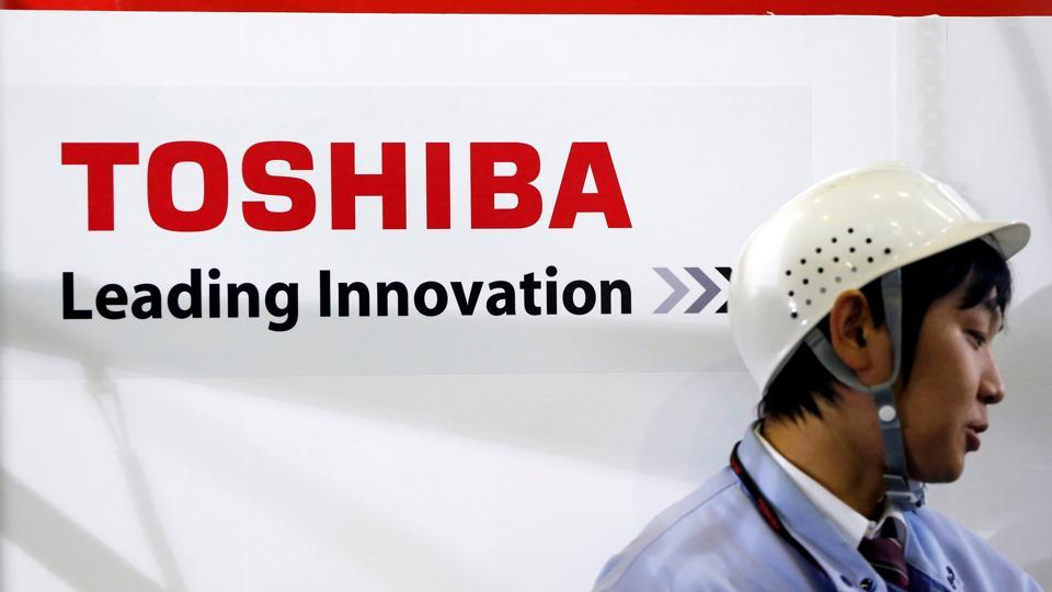 File photo of an employee standing next to a logo of Toshiba Corp in Yokohama, south of Tokyo, in  November 2012.