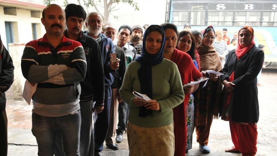 People stand outside a polling station in Jalandhar, Punjab.