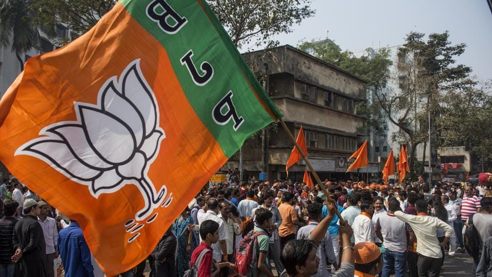 Party workers wave flags during a nomination filing rally in Mumbai.