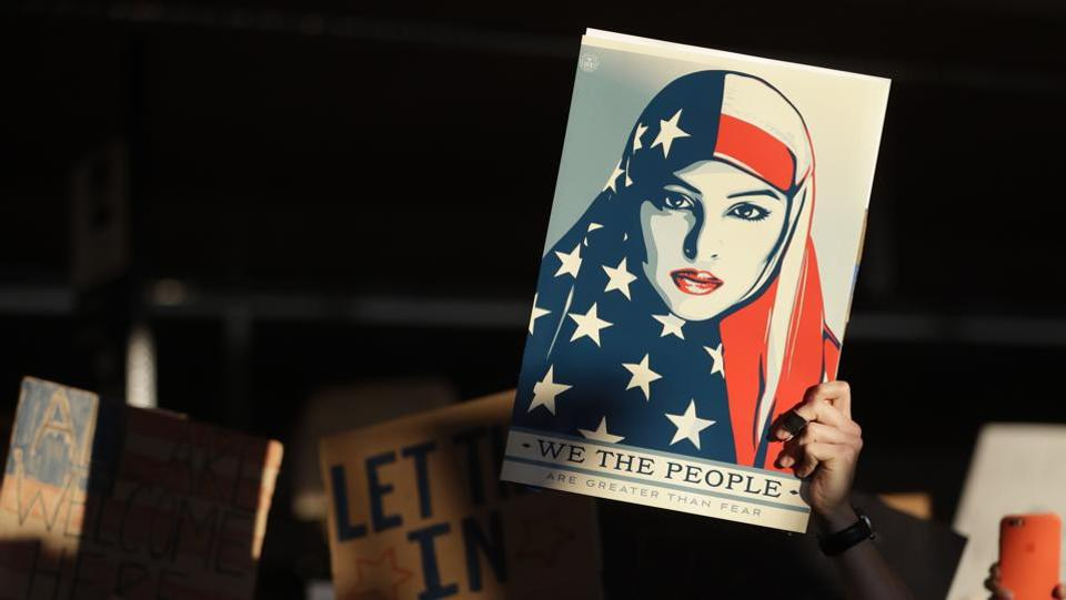 A protester holds up a sign at San Francisco International Airport during a demonstration to denounce President Donald Trump's executive order that bars citizens of seven predominantly Muslim-majority countries from entering the US.   (Marcio Jose Sanchez / AP)