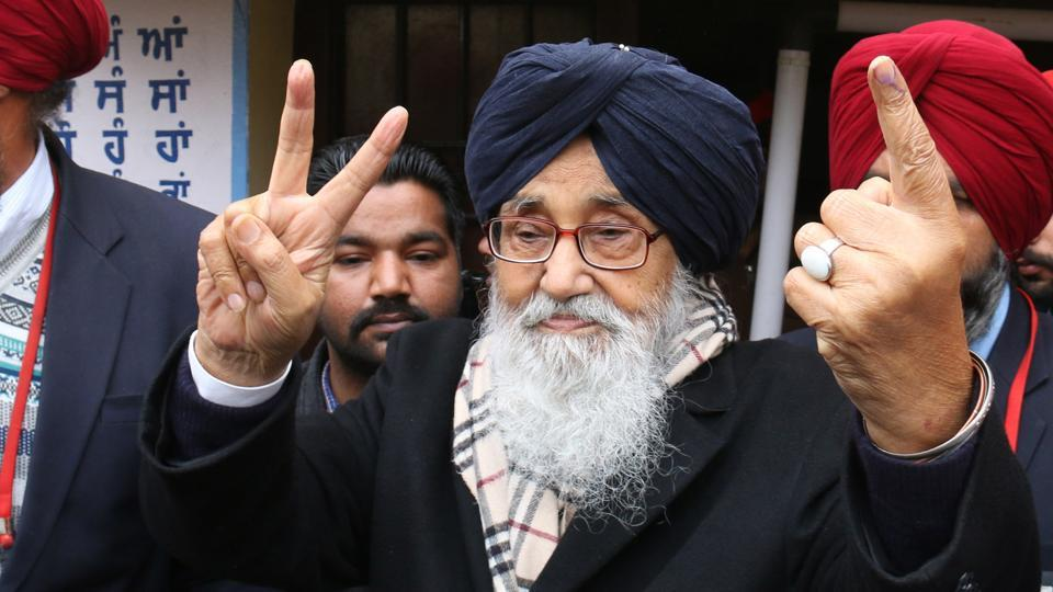 Chief minister Parkash Singh Badal showing the victory sign and his inked finger after casting his vote in Badal village in Lambi segment on Saturday.