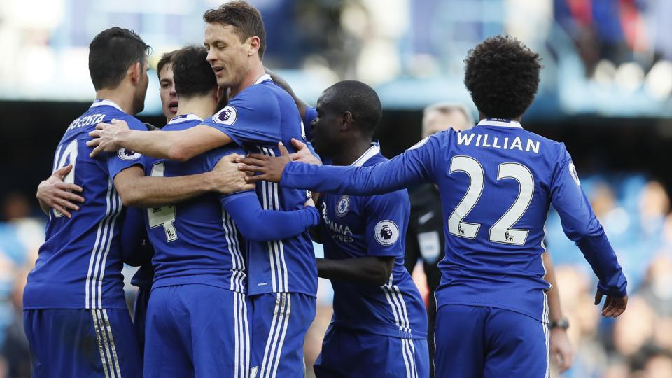 Chelsea FC's Cesc Fabregas, second left is mobbed by his teammates after scoring against Arsenal Football Club in Premier League.