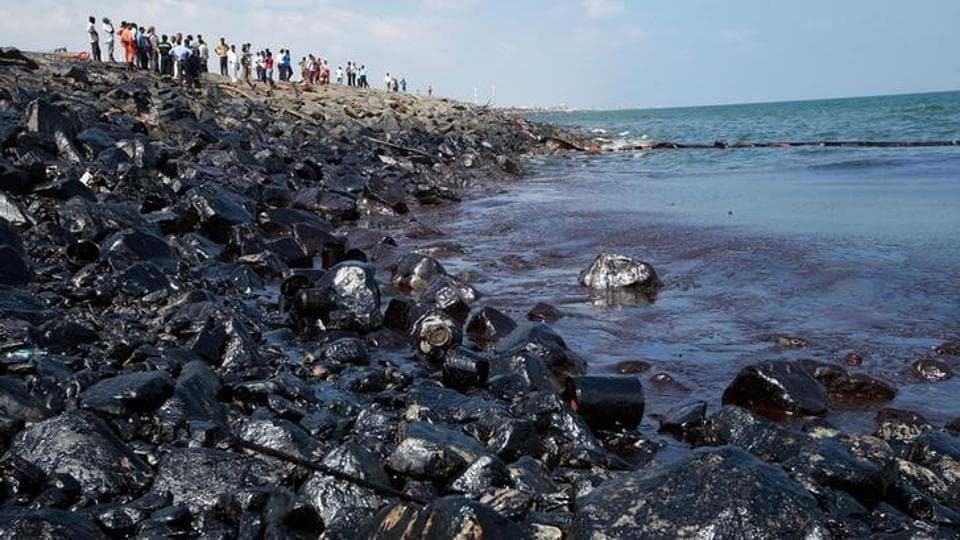 Emergency workers and locals stand along the shoreline of Ennore Port following a collision between two oil tankers, in Chennai.