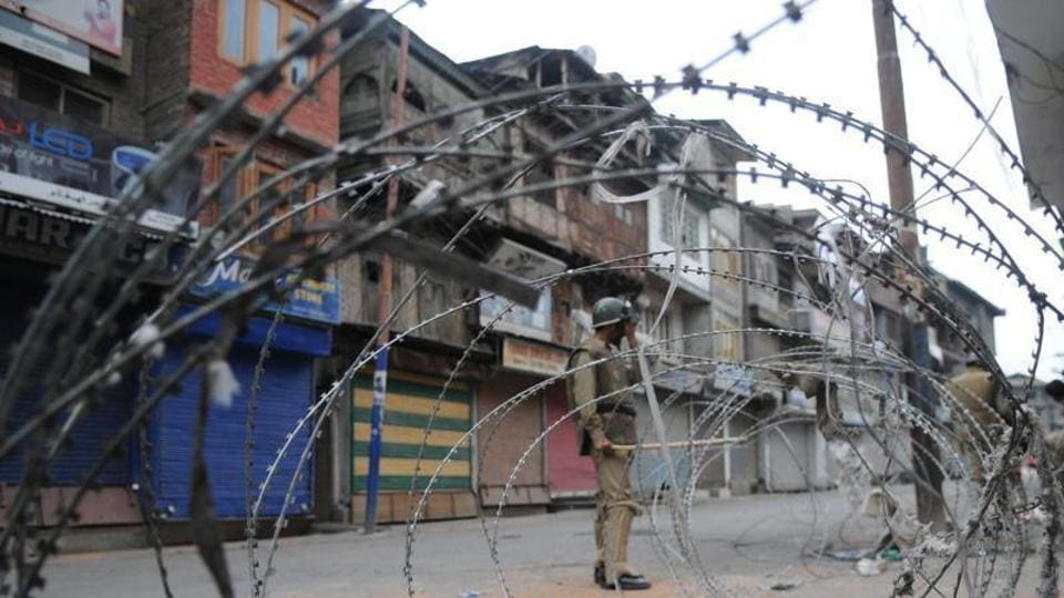 A Policeman stands near a barbed wire during curfew in Srinagar, 11 July 2016.