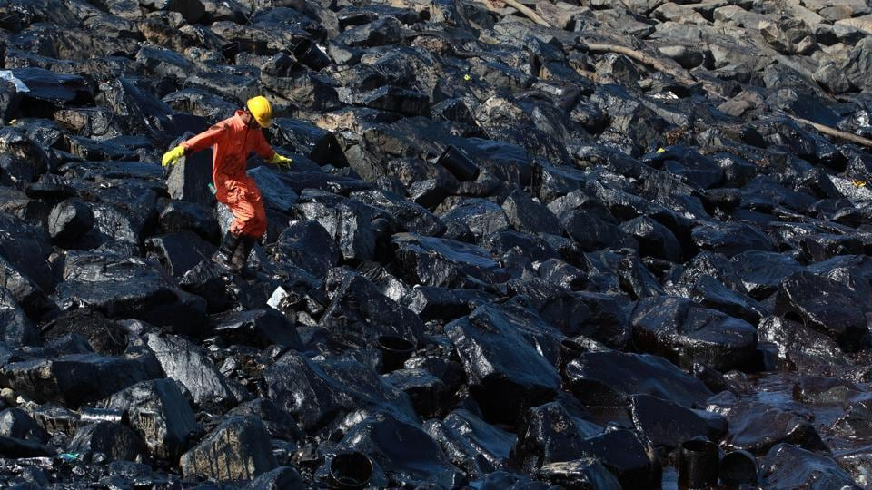 An emergency worker walks amidst oil deposits as he cleans oil from the shoreline of Ennore Port following a collision between two oil tankers, in Chennai, India.   (REUTERS)